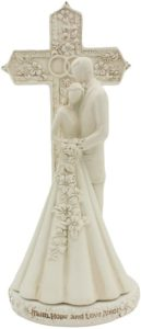 Ivory couple standing in front of an ornate cross