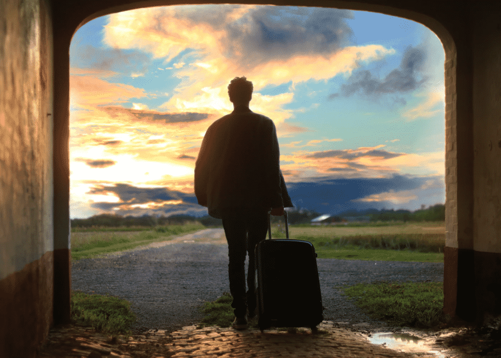 Man rolling luggage case walks into picturesque sunset