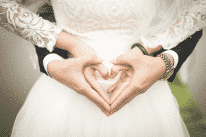 Married couple making heart symbol with their hands