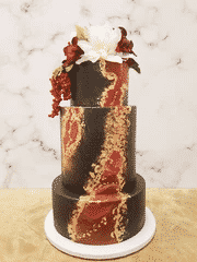 A red, black, and gold wedding cake covered in red and white flowers.